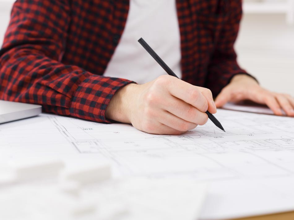 Serious young architect in casual working with blueprints in modern workplace interior, copy space, closeup